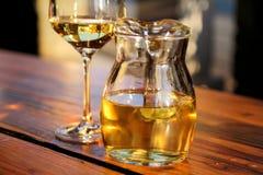 Fles wit wijn en glas op houten lijstbovenkant Glas gekoelde witte wijn op lijst dichtbij het strand Stock Foto