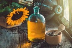 Fles zonnebloemolie, houten mortier van zaden en gele zonnebloem op houten lijst Stock Afbeeldingen