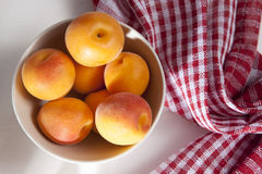 The Fleshy apricots in the bowl on the table. Fleshy apricots in the bowl on the table Stock Photo