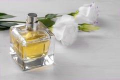 Flesje parfum en witte bloemen van eustoma op een witte houten achtergrond stock foto