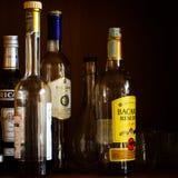 Flessen alcohol in een glasgeval Royalty-vrije Stock Afbeeldingen