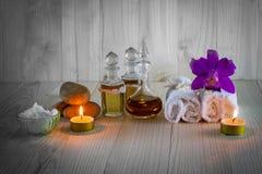 Flessen aromatische oliën met kaarsen, roze orchidee, stenen en witte handdoek op houten achtergrond met vignet Stock Foto's