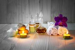 Flessen aromatische oliën met kaarsen, roze orchidee, stenen en witte handdoek op uitstekende houten achtergrond met vignet Royalty-vrije Stock Foto's