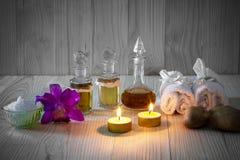 Flessen aromatische oliën met kaarsen, roze orchidee, stenen en witte handdoek op uitstekende houten achtergrond met vignet Stock Afbeeldingen