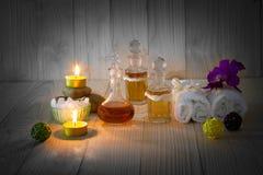 Flessen aromatische oliën met kaarsen, roze orchidee, stenen en witte handdoek op uitstekende houten achtergrond met vignet Royalty-vrije Stock Afbeeldingen