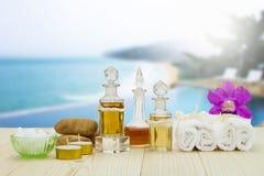 Flessen aromatische oliën met kaarsen, roze orchidee, stenen en witte handdoek op uitstekende houten vloer op vaag pool en strand Stock Foto's
