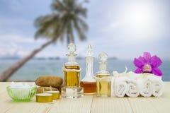 Flessen aromatische oliën met kaarsen, roze orchidee, stenen en witte handdoek op uitstekende houten vloer op vage strandachtergr Stock Afbeelding