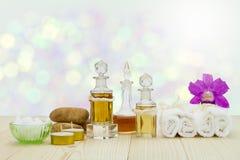 Flessen aromatische oliën met kaarsen, roze orchidee, stenen en witte handdoek op uitstekende houten vloer op vage bokeh achtergr Stock Afbeeldingen