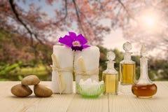 Flessen aromatische oliën met roze orchidee, stenen en witte handdoek op uitstekende houten vloer op vaag meer en bosachtergrond Stock Foto's
