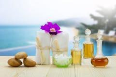 Flessen aromatische oliën met roze orchidee, stenen en witte handdoek op uitstekende houten vloer op vage pool en strandachtergro Stock Foto's