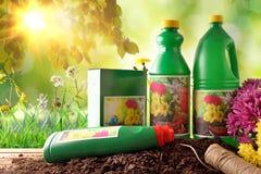 Flessen en containers van het tuinieren producten in aard met sunl Stock Foto's