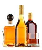 Flessen en glazen alcoholische dranken op wit royalty-vrije stock afbeeldingen