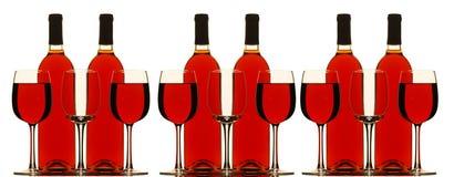 Flessen en Glazen die met rode wijn worden gevuld Royalty-vrije Stock Afbeelding