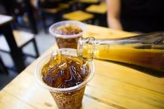 Flessen gietende cokes Stock Afbeeldingen