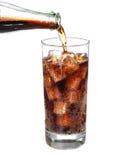 Flessen gietende cokes in drankglas met Geïsoleerde ijsblokjes Royalty-vrije Stock Foto
