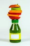 Flessen groene smoothie met stukken vers fruit op witte achtergrond Royalty-vrije Stock Foto's