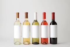 Flessen heerlijke wijnen met lege etiketten Stock Afbeeldingen