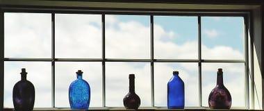 Flessen in het venster stock afbeelding
