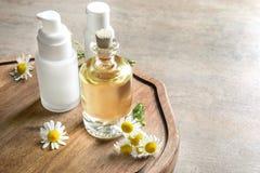 Flessen met cosmetischee producten en verse kamillebloemen op houten raad Stock Afbeelding