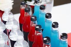 Flessen met kleurrijke dranken die zich op lijst bevinden stock afbeeldingen