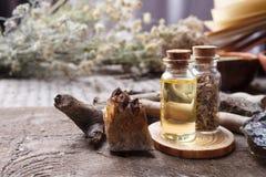 Flessen met kruiden, droge bloemen, stenen en magische voorwerpen op heksen houten lijst Geheim, esoterisch, waarzegging en wicca stock foto's