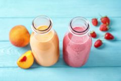 Flessen met yummy smoothie op lijst royalty-vrije stock afbeeldingen