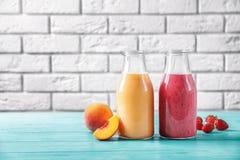 Flessen met yummy smoothie op lijst stock foto's