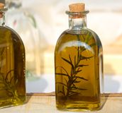 Flessen olijfolie met wilde Rosemary op smaak die worden gebracht die Stock Fotografie