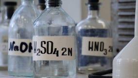 Flessen oplossingen op plank in laboratorium worden opgeslagen dat Flessen met chemische oplossingen van NaOH, H2so4 en HNO3 zwav royalty-vrije stock fotografie