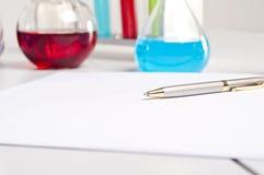 Flessen, pen, leeg document, werkplaats Stock Afbeeldingen
