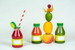Flessen smoothie met stro, verse appel, citroen, kalk, physalis, frambozen Royalty-vrije Stock Foto's