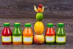 Flessen smoothie met verse appel, citroen, kalk, physalis, frambozen Stock Afbeeldingen