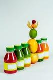 Flessen smoothie met verse appel, citroen, kalk, physalis, frambozen Stock Foto's