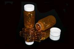 Flessen van grote, oranje capsules op zwarte spiegel royalty-vrije stock foto's