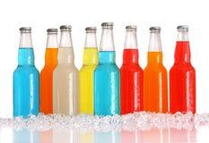 Flessen van veelkleurige dranken met ijs op wit Stock Foto's