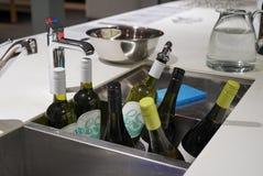 Flessen wijn die in een hoogtepunt van het gootsteenbad van ijs en water worden gekoeld stock afbeeldingen
