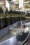 Flessen wijn in een bottelarij Stock Afbeeldingen