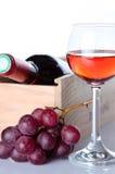 Flessen wijn in een houten doos met een glas van wijn en rode gra Royalty-vrije Stock Afbeeldingen
