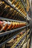 Flessen wijn van verschillende die kleuren in een kelder tijdens een voedsel en wijnmarkt worden getoond Stock Afbeeldingen