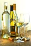 Flessen witte wijn met glazen Royalty-vrije Stock Afbeeldingen