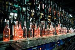 Flessenfabriek, rij van glasflessen Stock Afbeeldingen