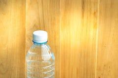 Flessenwater aan plastiek op de houten achtergrond wordt gemaakt die Het gebruiken van behang voor pakket of product, drugbeeld e Stock Foto