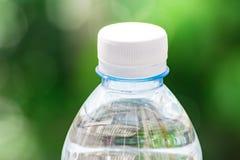 Flessenwater aan plastiek op hemel en boom onscherpe achtergrond wordt gemaakt die Het gebruiken van behang voor pakket of produc Royalty-vrije Stock Fotografie
