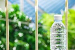 Flessenwater aan plastiek op hemel en boom onscherpe achtergrond wordt gemaakt die Het gebruiken van behang voor pakket of produc Stock Foto's