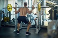 Flessione dei muscoli con il bilanciere Fotografia Stock Libera da Diritti
