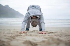 Flessione dell'uomo sulla spiaggia Fotografia Stock Libera da Diritti