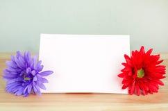 Fleur artificielle en pastel avec le papier de note blanc Photographie stock libre de droits