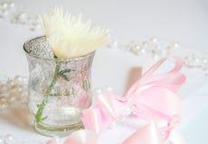 Fleur blanche dans un petit vase et un ruban rose d'arc images libres de droits