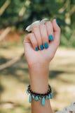 Fleur blanche de plumeria en main avec un bracelet de turquoise photo libre de droits