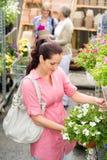 Fleur blanche de surfinia de prise de femme de jardinerie Photo stock